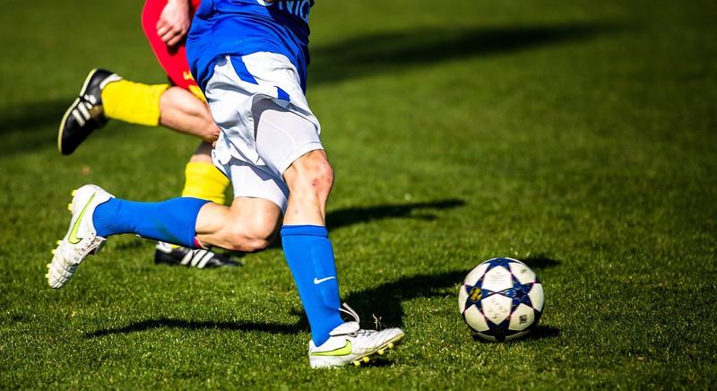 Fußballspieler werden hier im Zweikampf gezeigt