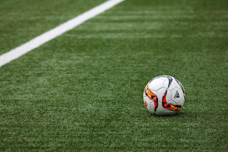 Fußballplatz aus Kunstrasen, auf dem ein Ball liegt
