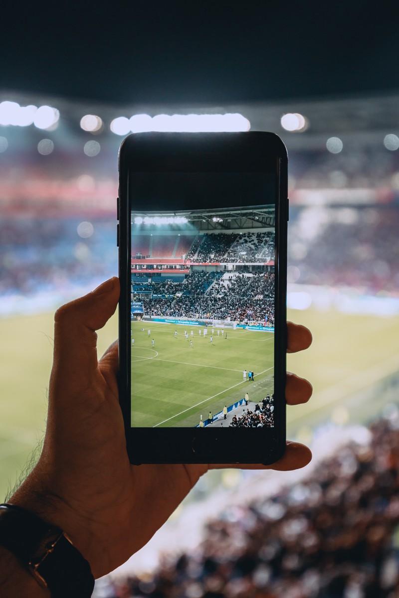 Man erkennt einen Mann, der ein Foto von dem laufenden Fußballspiel mit seinem Handy aufnimmt