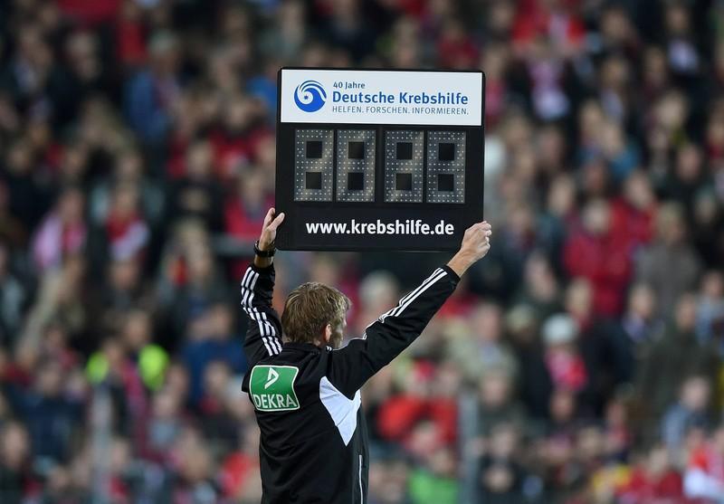 Der vierte Offizielle zeigt die Nachspielzeit auf einer Tafel an