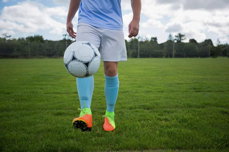 Ein Fußballer jongliert den Ball mit en Füßen