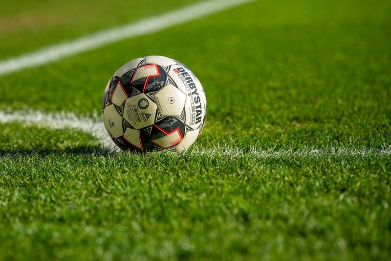Ein Fußball liegt am Eckpunkt eines Fußballplatzes