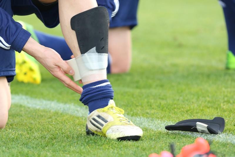 Ein Fußballspieler bindet sich die Schienbeinschoner um
