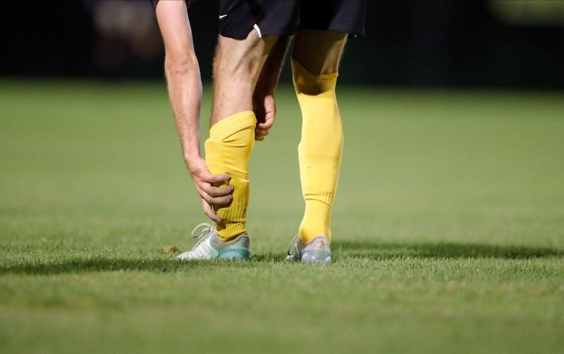 Ein Fußballspieler richtet sich die Stutzen