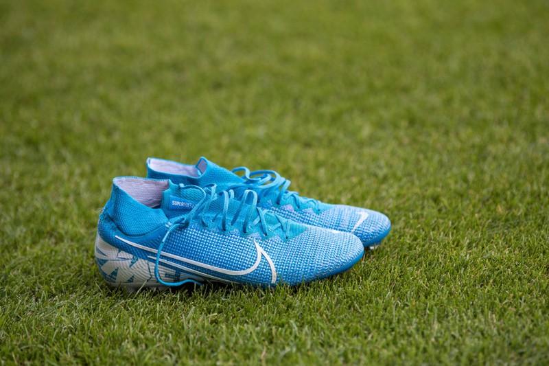 Ein paar Fußballschuhe stehen auf kurz gemähtem Rasen