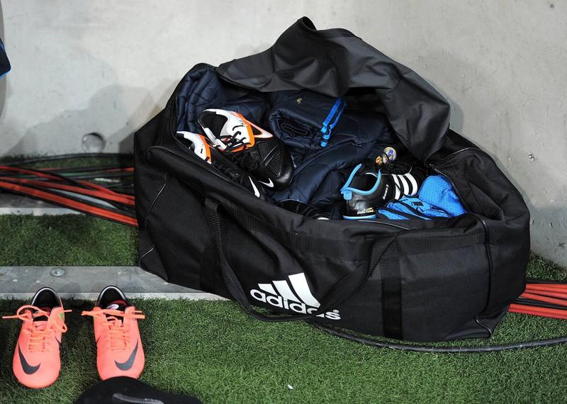 Eine gefüllte Sporttasche mit Fußballschuhen steht an der Seite
