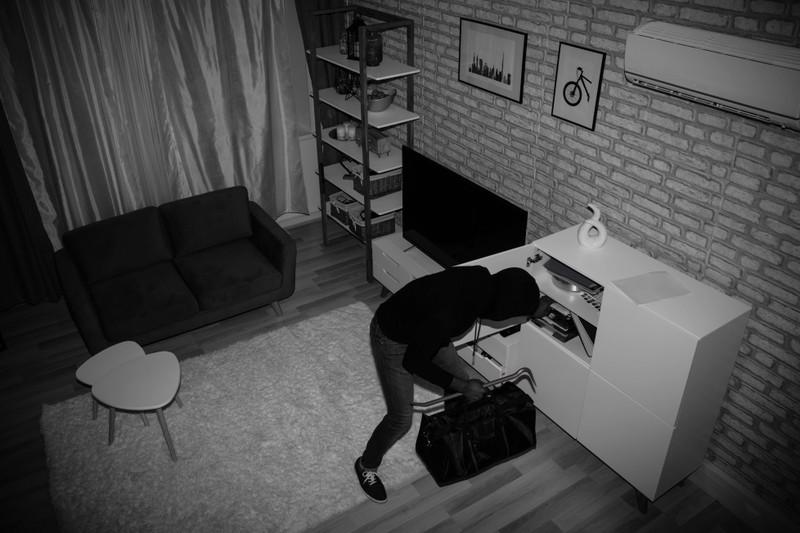Ein Einbrecher stiehlt etwas aus einem Haus